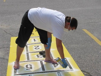 Woman painting playground stencils on pavement