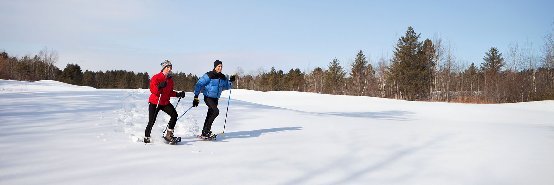 couple snowshoeing through on open field on a sunny winter day