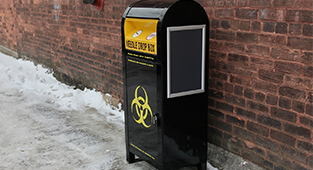 An black and yellow safe sharps disposal bin in front of a brick wall